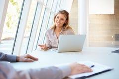 Geschäftsleute, die Sitzung um Tabelle im modernen Büro haben Stockbilder