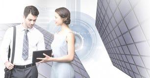 Geschäftsleute, die Tablette und hohe Gebäude mit Technologieformhintergrund betrachten Lizenzfreie Stockfotos
