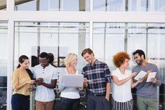 Geschäftsleute, die Technologien bei der Diskussion im Balkon einsetzen Lizenzfreies Stockbild