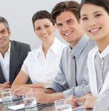 Geschäftsleute, die um einen Konferenztisch sitzen Stockbilder