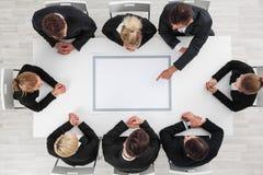 Geschäftsleute, die um leere Tabelle sitzen stockbild