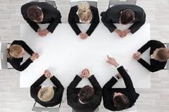 Geschäftsleute, die um leere Tabelle sitzen stockfotografie