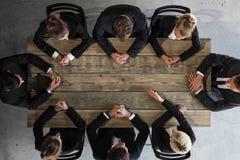 Geschäftsleute, die um Tabelle sitzen lizenzfreies stockfoto