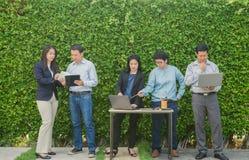 Geschäftsleute, die Unternehmens-Digital-Gerät-Verbindungs-Konzept auf Baumwand treffen stockfotos