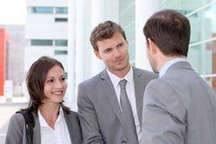 Geschäftsleute, die vor Büro zusammentreten Stockfoto