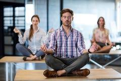 Geschäftsleute, die Yoga auf Tabelle durchführen lizenzfreies stockfoto