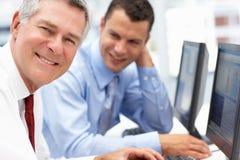 Geschäftsleute, die zusammen an Computer arbeiten Stockbilder