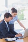 Geschäftsleute, die zusammen mit einem Laptop arbeiten Lizenzfreie Stockfotos