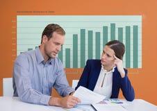 Geschäftsleute an einem Schreibtisch, der ein Papier gegen orange Hintergrund mit grünen Grafiken betrachtet Stockfotos