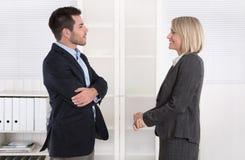 Geschäftsleute im Anzug und im Kleid zusammen sprechend: leichte Unterhaltung Lizenzfreie Stockfotos