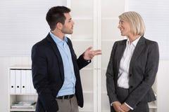 Geschäftsleute im Anzug und im Kleid zusammen sprechend: leichte Unterhaltung Stockbilder