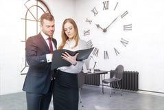 Geschäftsleute im Büro mit großer Wanduhr Stockbild