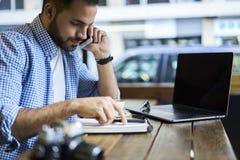 Geschäftsleute im blauen Hemd, das im Studio unter Verwendung des Radioapparates 5G und des Laptops mit Spott herauf Schirm sitzt Lizenzfreie Stockfotos