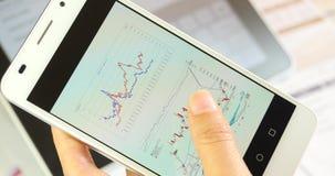 Geschäftsleute 4k, die Finanzkreisdiagramme u. Vorrattendenz auf SmartPhone grasen stock video footage