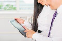Geschäftsleute kleideten im Weiß unter Verwendung des Tabletten-PC im Büro an Lizenzfreie Stockbilder