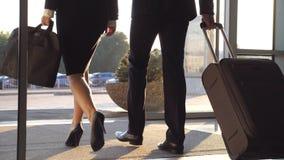 Geschäftsleute lassen Flughafen und das Gehen mit ihrem Gepäck an der Stadtstraße Unerkennbarer Mann und Frau in den Fersen stock video
