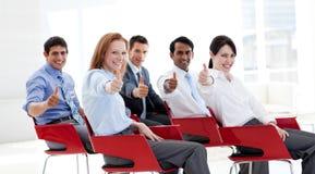 Geschäftsleute mit den Daumen oben bei einer Konferenz Lizenzfreie Stockfotos