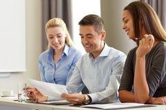 Geschäftsleute mit den Papieren, die im Büro sich treffen lizenzfreies stockfoto