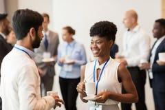 Geschäftsleute mit Konferenzausweisen und -kaffee stockbilder