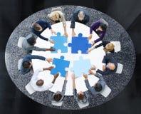 Geschäftsleute mit Puzzlespiel-Stücken und Teamwork-Konzept Lizenzfreie Stockfotos