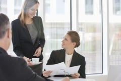 Geschäftsleute mit Schreibarbeit während der Kaffeepause Lizenzfreie Stockfotografie