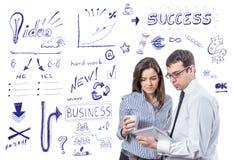 Geschäftsleute mit Tablette über Erfolgssymbolen Lizenzfreies Stockfoto