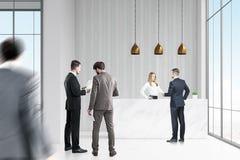Geschäftsleute nähern sich Aufnahmeschreibtisch im Büro Stockbild