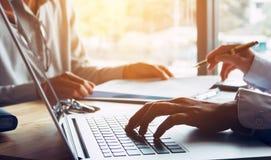 Geschäftsleute oder Doktor, die mit Kunden sprechen und Laptop a verwenden lizenzfreie stockbilder