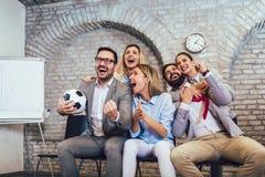 Geschäftsleute oder Fußballfane, die Fußball im Fernsehen aufpassen und Sieg feiern Freundschaft, Sport und Unterhaltungskonzept stockbild