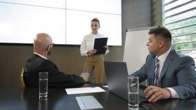 Geschäftsleute tun sich die Diskussion in den Sitzungsdokumenten und -ideen in einem modernen Büro in der Zeitlupe zusammen stock footage
