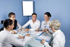 Geschäftsleute um eine Tabelle bei der Sitzung Lizenzfreie Stockbilder