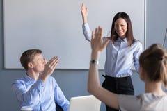 Geschäftsleute und weiblicher Teamleiter, die Handdas ausdrücken anheben lizenzfreie stockfotos