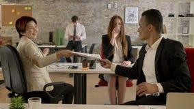 Geschäftsleute von Mischethnie arbeitend im Büro, schwarzer Mann, der zu den asiatischen Frauendokumenten, jeder beschäftigt gibt stock video
