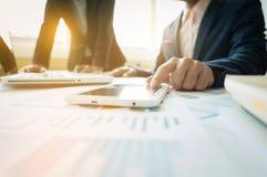 Geschäftsleute, welche die Diagramme und die Diagramme zeigen das Res besprechen Stockfotografie