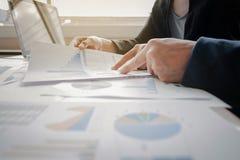 Geschäftsleute, welche die Diagramme und die Diagramme zeigen das Res besprechen Stockfotos