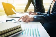 Geschäftsleute, welche die Diagramme und die Diagramme zeigen das Res besprechen Lizenzfreie Stockfotografie