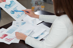 Geschäftsleute, welche die Diagramme und die Diagramme zeigen die Ergebnisse ihrer erfolgreichen Teamwork besprechen Stockbild