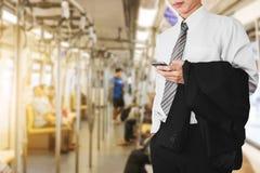Geschäftslokalangestellter, der Smartphone im U-Bahn- oder Himmelzug, gehend, am Sonnenaufgangmorgen zu arbeiten verwendet lizenzfreies stockfoto