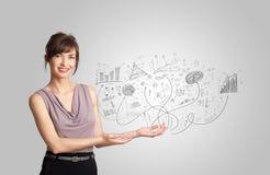 Geschäftsmädchen, das Hand gezeichnete Skizzendiagramme und -diagramme darstellt Stockbilder