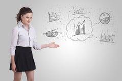 Geschäftsmädchen, das Hand gezeichnete Skizzendiagramme und -diagramme darstellt Lizenzfreie Stockfotos