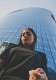 Geschäftsmädchen in einer schwarzen Kleidernahaufnahme auf Hintergrund des modernen Gebäudes Lizenzfreies Stockbild
