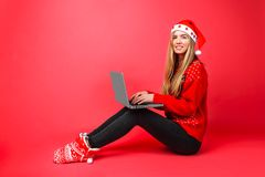 Geschäftsmädchen im roten sitzenden Arbeiten der Strickjacke und Sankt-Hutes mit Laptop auf rotem Hintergrund lizenzfreie stockfotos