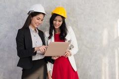 Geschäftsmädchen und -ingenieur mit asiatischen Leuten arbeiten mit Laptop AR Stockfotos