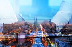 Geschäftsmänner übergibt unterzeichnende Dokumente auf Riad-Skylinestadt scape stockfotografie