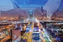 Geschäftsmänner übergibt unterzeichnende Dokumente auf Riad-Skylinestadt scape stockbilder