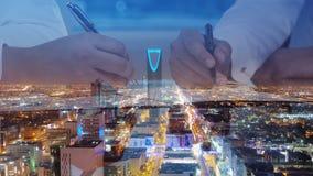 Geschäftsmänner übergibt unterzeichnende Dokumente auf Riad-Skylinestadt scape stockfotos