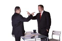 Geschäftsmänner, die über dem Schreibtisch kämpfen Stockfotos