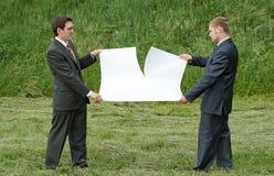 Geschäftsmänner, die Blatt Papier zerreißen Stockfotografie
