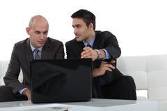 Geschäftsmänner, die einen Laptop betrachten Stockfotos
