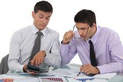 Geschäftsmänner, die Ergebnisse nachforschen Stockbild